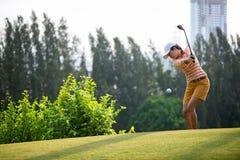 击中芯片高尔夫球的亚裔女子高尔夫球运动员对在绿色的孔与高尔夫俱乐部在晴天,拷贝空间 图库摄影