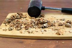 击碎了在其次桌上的所有坚果是在木桌砧板的锤子 免版税库存图片