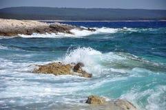 击碎在一个多岩石的海滩的通知 免版税库存照片
