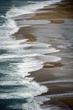 击碎在沙子的蓝色波浪 免版税图库摄影