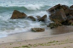 击碎在石头的波浪 免版税库存图片