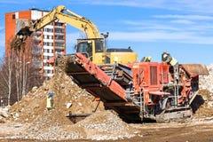 击碎混凝土的履带牵引装置流动压碎器和挖掘机 库存图片