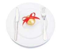刀叉餐具叉子刀子牌照和复活节金黄鸡蛋。 库存照片