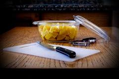 刀子、切板、削皮器和碗用被切的土豆在厨房用桌上 库存图片