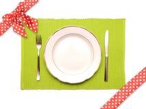 刀子、叉子和在一块绿色餐巾的空白牌照 库存照片