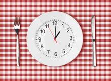 刀子、白色板材有时钟表盘的和叉子在红色野餐桌上 免版税库存图片