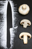 刀子剪影用面粉和slieced蘑菇在黑色页岩背景 库存图片
