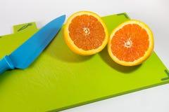 刀子和切片桔子 免版税库存照片