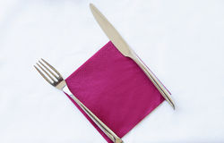 刀子和叉子在紫色餐巾在白色背景 库存照片