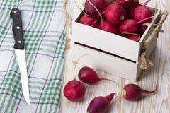 刀子和红色萝卜在一个木箱 库存图片