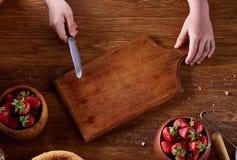 刀子在女孩切在木桌,顶视图, selctive焦点上的` s手上一个新鲜的草莓 免版税图库摄影