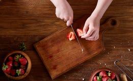 刀子在女孩切在木桌,顶视图, selctive焦点上的` s手上一个新鲜的草莓 图库摄影