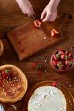 刀子在女孩切在木桌,顶视图, selctive焦点上的` s手上一个新鲜的草莓 库存图片