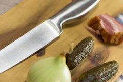 刀子,烟肉,黄瓜,葱,木板-特写镜头 库存图片