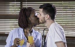 分享一个亲吻的愉快的混合的族种夫妇早晨 免版税库存照片