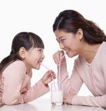 分享一杯牛奶,演播室射击的母亲和女儿 免版税库存照片