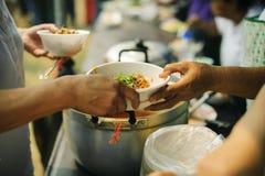 分享为了贫寒的食物的概念能缓和饥饿:哺养帮助的贫穷的社会问题:捐赠食物给人  免版税图库摄影