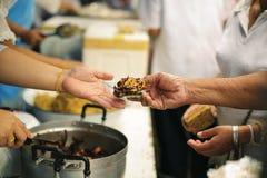 分享为了贫寒的食物的概念能缓和饥饿:哺养帮助的贫穷的社会问题:捐赠食物给人  图库摄影