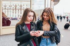 分享在一个巧妙的电话的两个愉快的妇女朋友社会媒介户外在城市 有手机的两个少妇 库存图片
