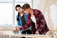 分享工具的年轻夫妇,当工作在他们新的家的改善时 图库摄影