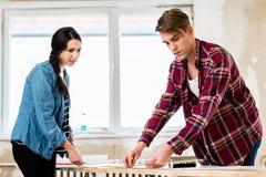 分享工具的年轻夫妇,当工作在他们的房子的改善时 免版税库存图片