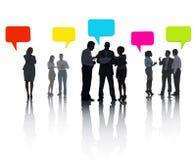 分享想法的小组不同的商人与五颜六色的讲话泡影 免版税库存照片