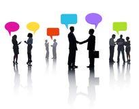 分享想法的小组不同的商人与五颜六色的讲话泡影 免版税图库摄影