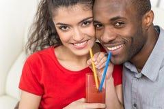 分享杯橙汁和看照相机的年轻夫妇 库存图片