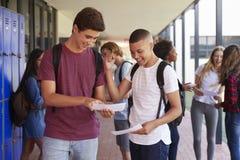 分享检查的愉快的十几岁的男孩导致学校走廊 免版税库存照片