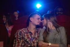分享浪漫片刻的年轻爱恋的夫妇在戏院 免版税库存图片