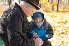 分享片剂个人计算机的祖父和孙子 免版税图库摄影