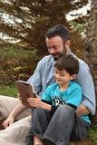分享片剂的父亲和儿子 免版税库存照片