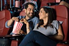 分享玉米花的夫妇在电影 免版税库存图片