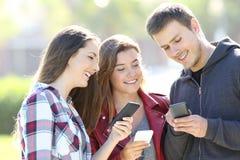 分享电话内容的三个青少年的朋友 免版税库存照片