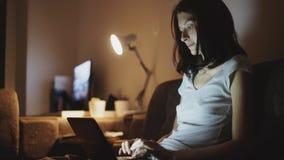 分享社会媒介的年轻可爱的妇女在家使用在便携式计算机上在夜间 免版税图库摄影