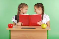 分享秘密的两所学校女孩坐在从书的一张书桌 免版税库存图片