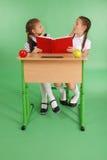 分享秘密的两所学校女孩坐在从书的一张书桌 图库摄影
