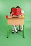 分享秘密的两所学校女孩坐在从书的一张书桌 免版税库存照片