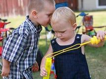 分享秘密的可爱的孩子 图库摄影