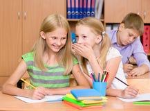 分享秘密的女孩在教室 免版税图库摄影