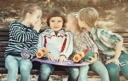 分享秘密的孩子如谈话室外 库存图片