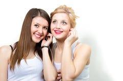 分享耳机的两个俏丽的妇女朋友 图库摄影