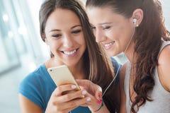 分享耳机的俏丽的女孩 免版税库存照片
