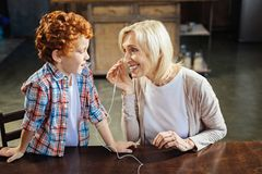 分享耳机的红头发人小男孩与老婆婆 免版税图库摄影