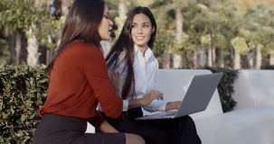 分享膝上型计算机的两名俏丽的妇女户外 免版税图库摄影