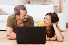 分享膝上型计算机的愉快的夫妇 库存图片