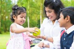 分享苹果的印地安女孩与家庭 免版税图库摄影