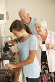 分享茶的少年孙女与祖母在厨房里 库存照片