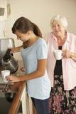 分享茶的少年孙女与祖母在厨房里 免版税库存图片