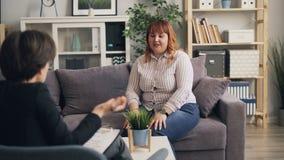 分享问题的肥胖女孩与谈和打手势在长沙发的治疗师开会 影视素材